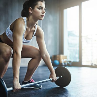 Shot of a sporty young woman working out with a barbell at the gym